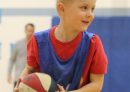 Boy holding a basketball. He has a huge smile and a glint in his eye.