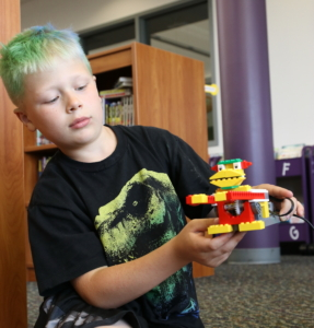 A boy with dyed green hair shows off his Monkey Robot.
