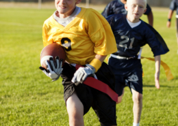 A young flag football player goes for the touchdown.