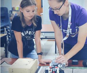 YEL Robotics teacher helps student with a challenge.
