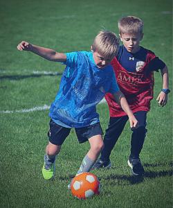 YEL soccer classes for kids. Two kiddos battling for the ball.