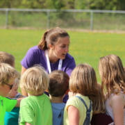 Coach giving pep talk to soccer team.Adult supervision minimizes risky behavior.