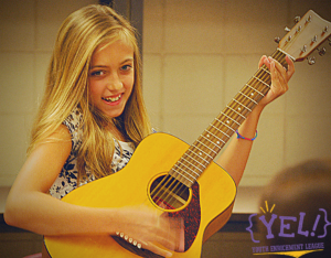 Girl smiling while playing guitar
