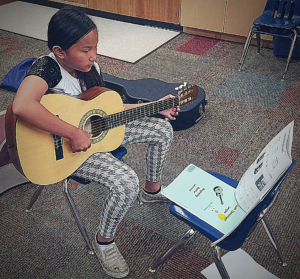 Young musician playing guitar looking at her guitar music.