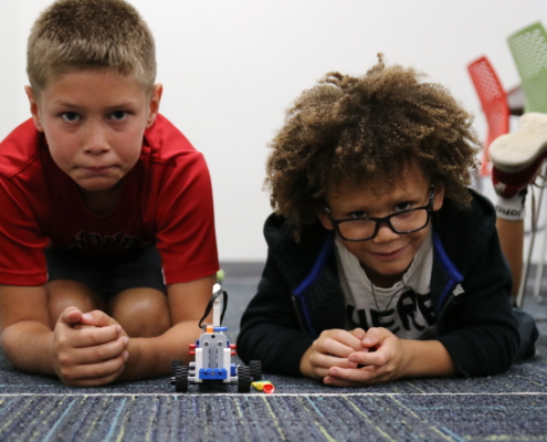 Two Brick Builder students prepare to race their car made out of LEGO Bricks.