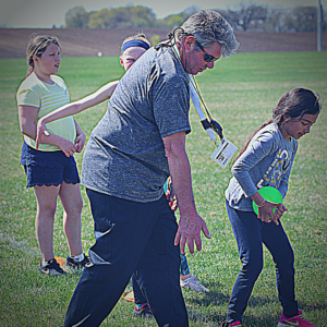 Dynamic coach showing a student how to throw the discus.